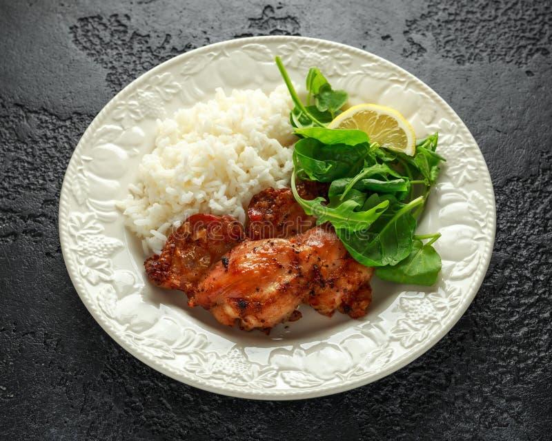 Зажаренные в духовке бескостные skinless бедренные кости цыпленка с рисом и зелеными овощами смешивают стоковое фото rf