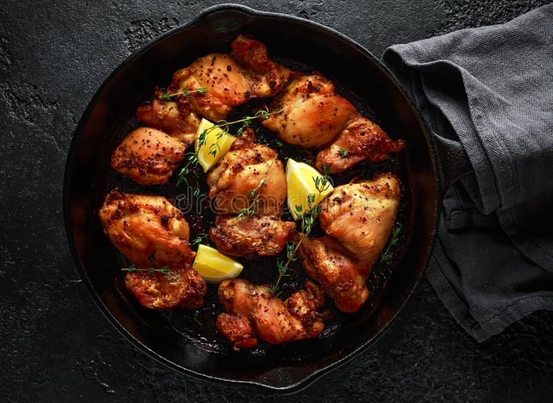 Зажаренные в духовке бескостные skinless бедренные кости цыпленка в шлихте лимона, который и тимиана служат в винтажном skillet л стоковая фотография