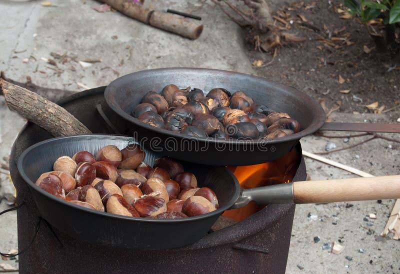 зажаренные в духовке каштаны Каштаны жаря в духовке в пламенах огня стоковая фотография rf