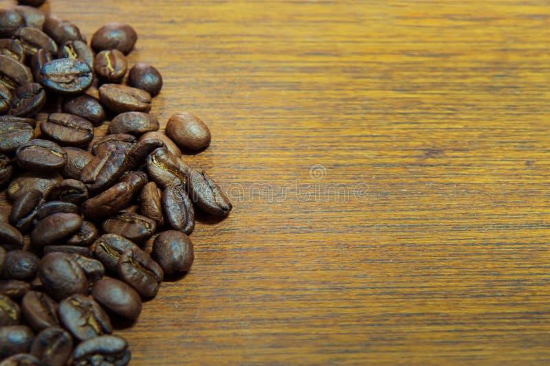 Зажаренные в духовке кофейные зерна на изображении деревянного конца tablemacro поднимающем вверх для bac стоковая фотография rf