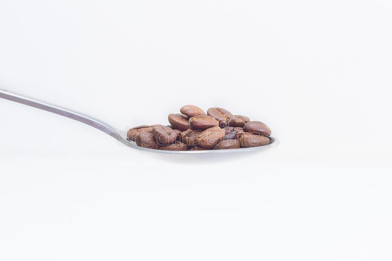 Зажаренные в духовке кофейные зерна в нержавеющей ложке на белом spac предпосылки стоковое изображение