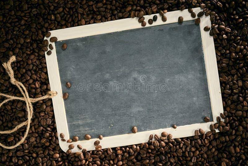 Зажаренные в духовке кофейные зерна обрамляя пустой винтажный шифер стоковое изображение rf