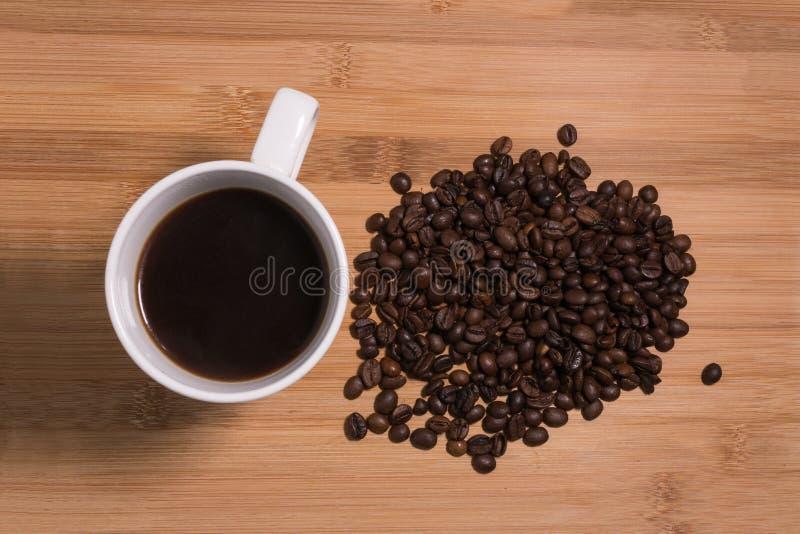 Зажаренные в духовке кофейные зерна с свежей чашкой кофе надземной на естественной деревянной предпосылке стоковые фотографии rf