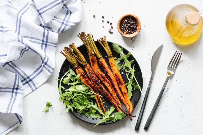 Зажаренные в духовке моркови и свежий зеленый вегетарианский салат стоковые изображения