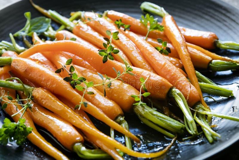 Зажаренные в духовке моркови младенца с травами на черном Blate стоковые изображения