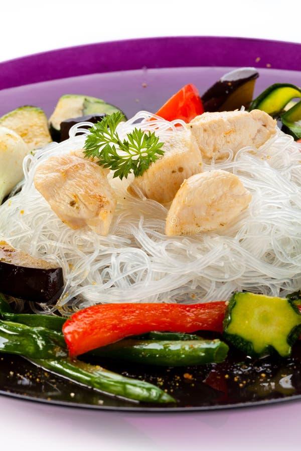 Зажаренные в духовке мясо, лапши риса и овощи на белизне стоковые изображения