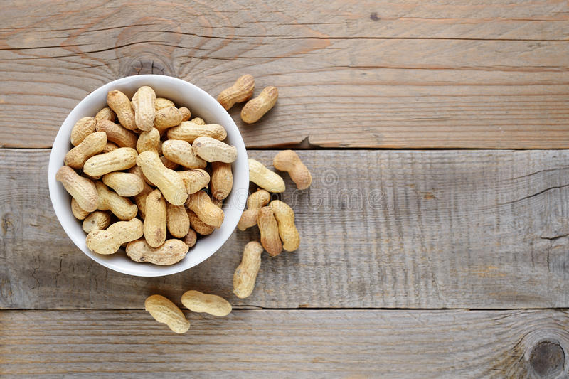 Зажаренные в духовке арахисы в шаре на деревянном столе стоковые фото