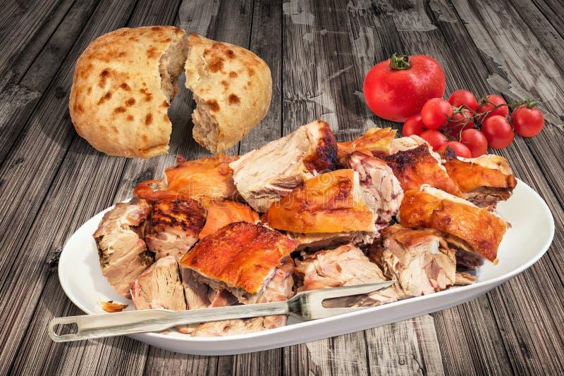 Зажаренные в духовке вертелом куски плеча свинины, который служат с сорванными Flatbread Pitta и пуком томатов вишни на старой вы стоковое фото