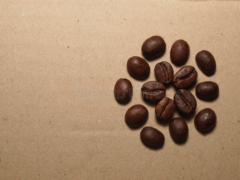 Зажаренные в духовке кофейные зерна на бумажной текстуре стоковое изображение rf