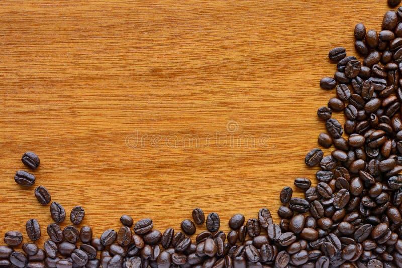 Зажаренные в духовке кофейные зерна на деревянной предпосылке - граничьте дизайн стоковая фотография