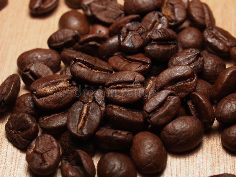 Зажаренные в духовке кофейные зерна на деревянной текстуре стоковые фото