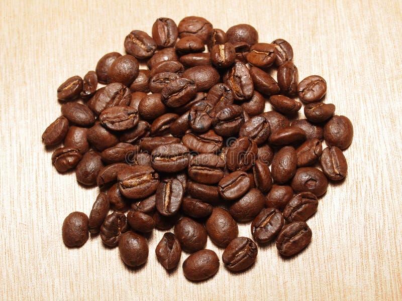 Зажаренные в духовке кофейные зерна на деревянной текстуре стоковые фотографии rf