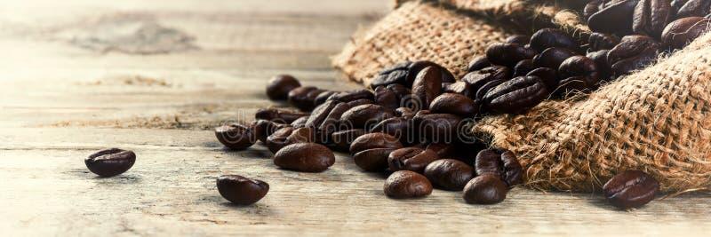 зажаренные в духовке кофейные зерна на старой деревянной предпосылке стоковая фотография rf