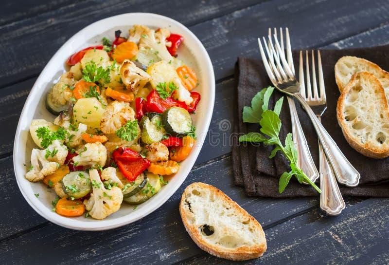 Зажаренные в духовке овощи - цукини, цветная капуста, картошки, моркови, луки, перцы, на овальном блюде стоковые изображения