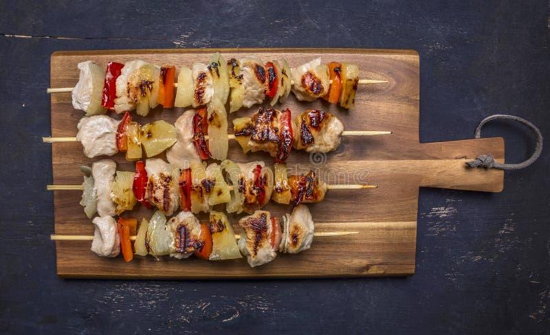 Зажаренные в духовке kebabs на разделочной доске с концом взгляд сверху предпосылки соуса деревянным деревенским вверх стоковая фотография rf
