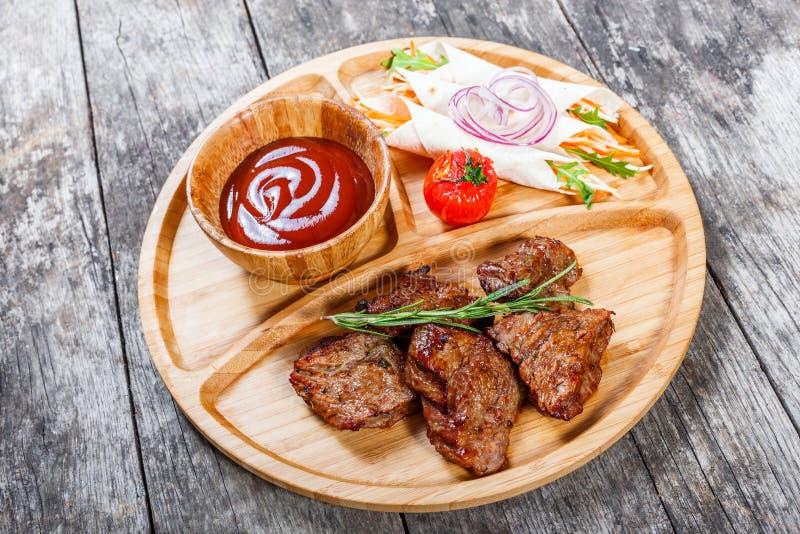 Зажаренные говядина и овощи с свежим салатом и соусом bbq на разделочной доске на деревянном конце предпосылки вверх стоковые изображения
