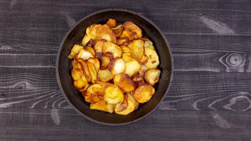 Зажаренные домодельные картофельные чипсы в винтажном античном лотке чугуна на деревянной деревенской предпосылке стоковое изображение rf