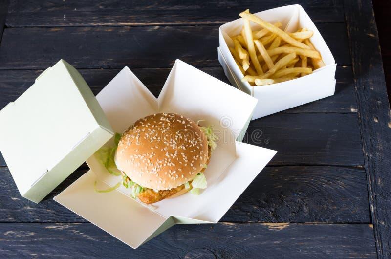 Зажаренные картошки и гамбургер Черная деревянная предпосылка стоковое изображение