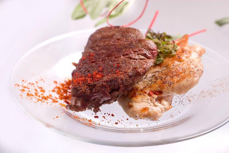 Зажаренные куриная грудка и свиная отбивная со стейком и травами мяса говядины в прозрачной плите стоковая фотография rf