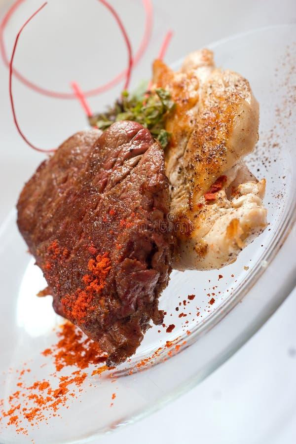Зажаренные куриная грудка и свиная отбивная со стейком и травами мяса говядины в прозрачной плите стоковые фотографии rf