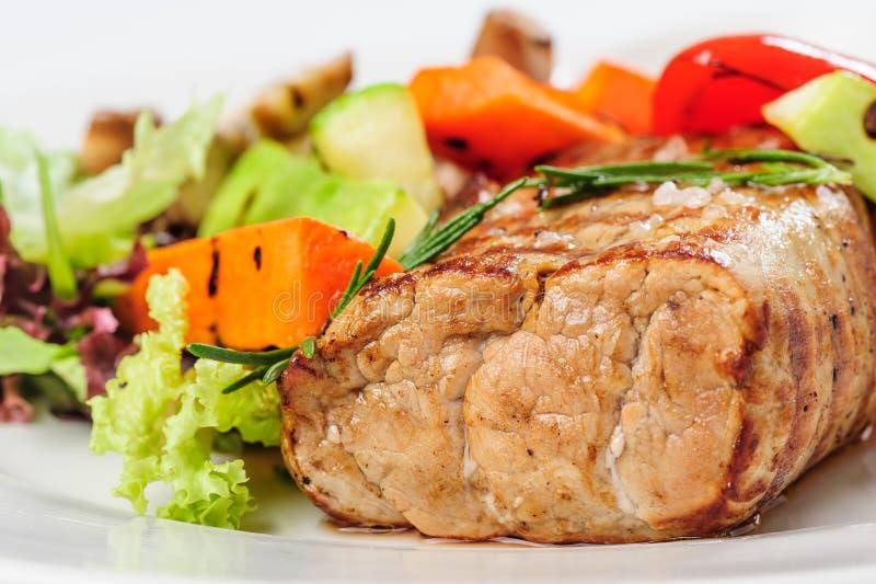 Зажаренные мясо и овощи свинины на плите стоковые фото