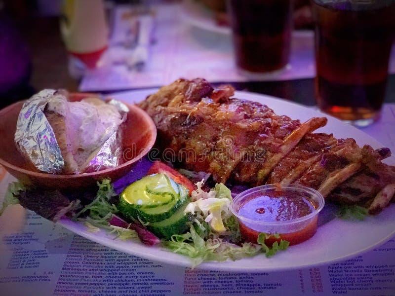 Зажаренные нервюры свинины запасные с салатом и картошкой на стороне стоковые изображения rf