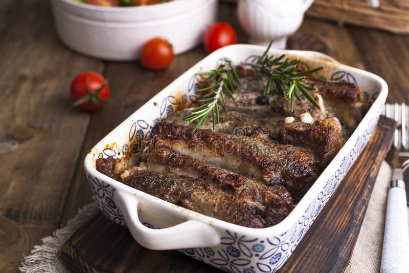 Зажаренные нервюры свинины Мясо со специями и травами в блюдах на деревянной предпосылке Обед для барбекю Открытый космос для тек стоковые изображения