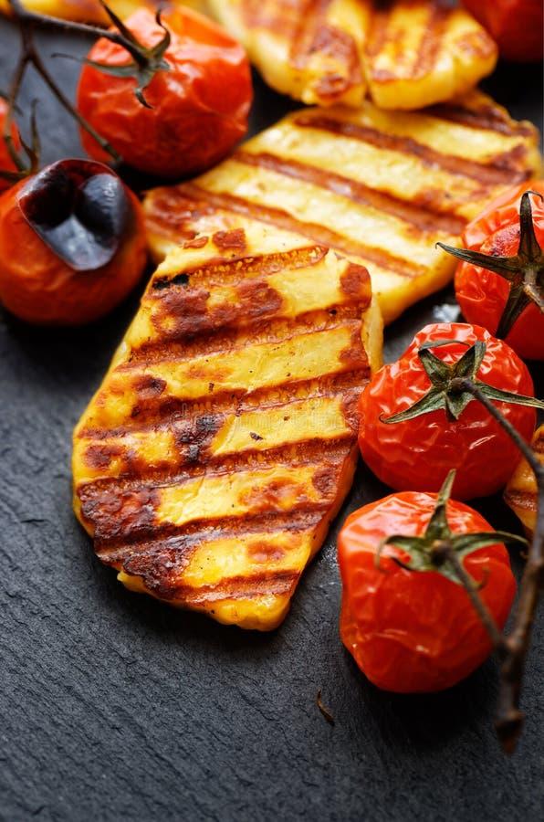 Зажаренные овощи с сыром halloumi на черной предпосылке стоковая фотография