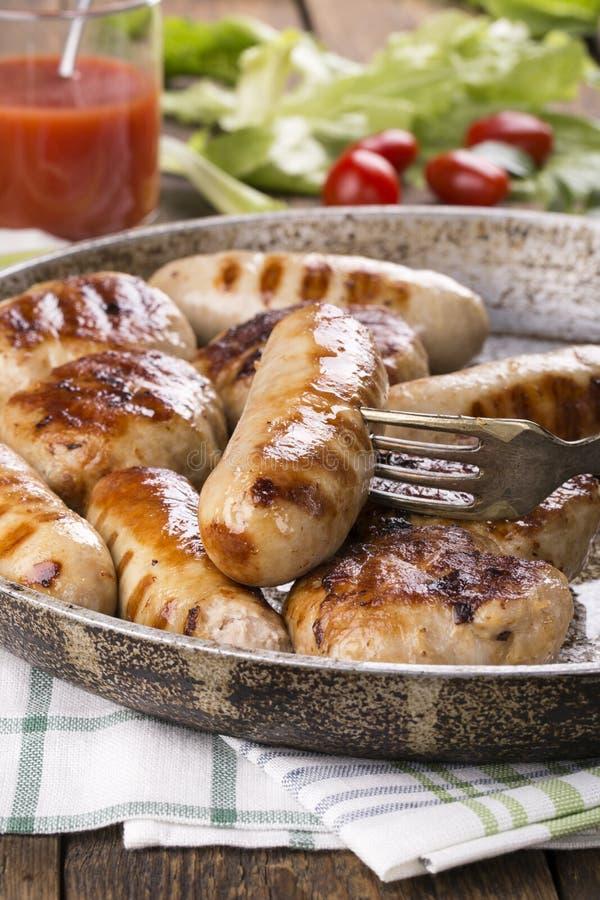Зажаренные сосиски и бургеры цыпленка стоковое изображение