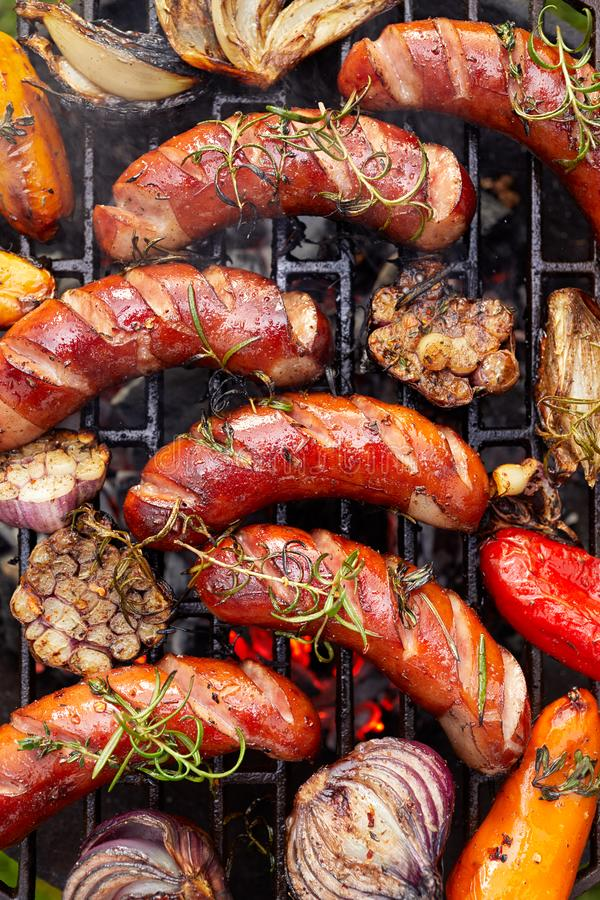 Зажаренные сосиски и овощи с специями добавлению и свежими травами на плите гриля стоковое изображение rf