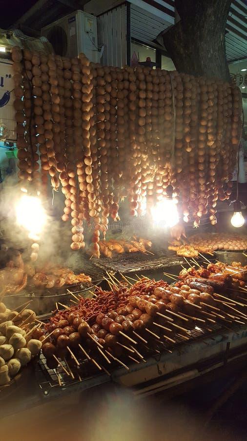 Зажаренные сосиски на плите, много сосисок аппетитны на тележке еды, традиционной тайской еде, курят жарком еды улицы, который Th стоковое изображение rf