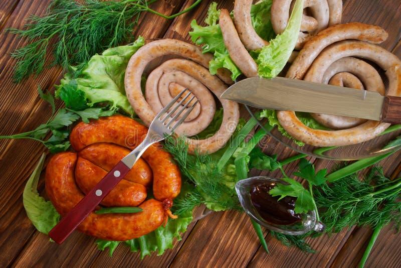 Зажаренные сосиски свинины, нож, вилка, соус в кастрюльке и плюшки мозоли на деревянной поверхности доск сосны Рядом салат, стоковая фотография