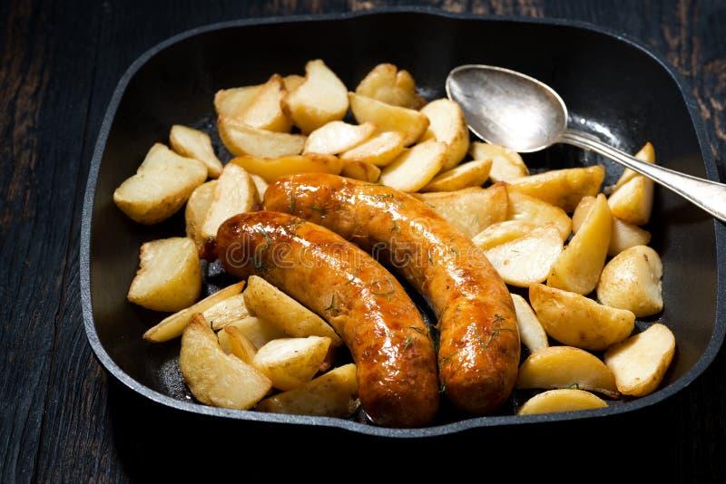 Зажаренные сосиски свинины с картошками в сковороде, горизонтальной стоковые фотографии rf