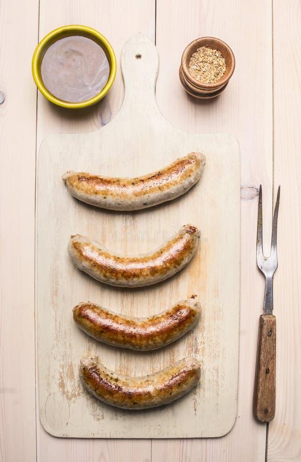 Зажаренные сосиски с вилкой зажарили мясо, соус и специи на белом деревенском взгляд сверху предпосылки стоковое фото rf