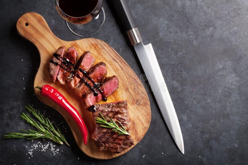 Зажаренные стейк striploin и красное вино стоковые фото