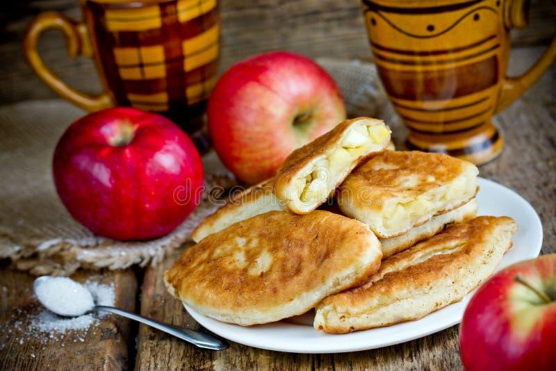 Зажаренные яблочные пироги от теста дрожжей заполненного с кусками яблока стоковые фотографии rf