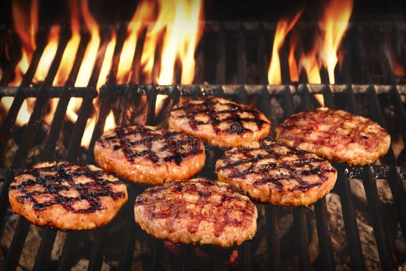 Зажаренные BBQ пирожки бургеров на горячем пламенеющем гриле стоковые изображения rf