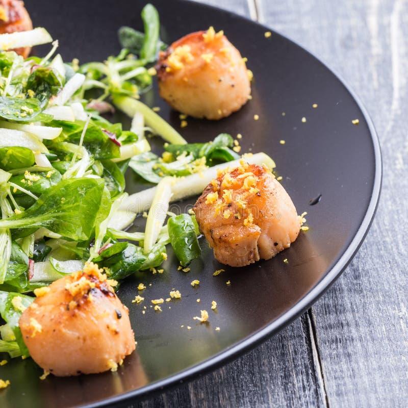 Зажаренные scallops с кудрявым зеленым салатом стоковые фотографии rf