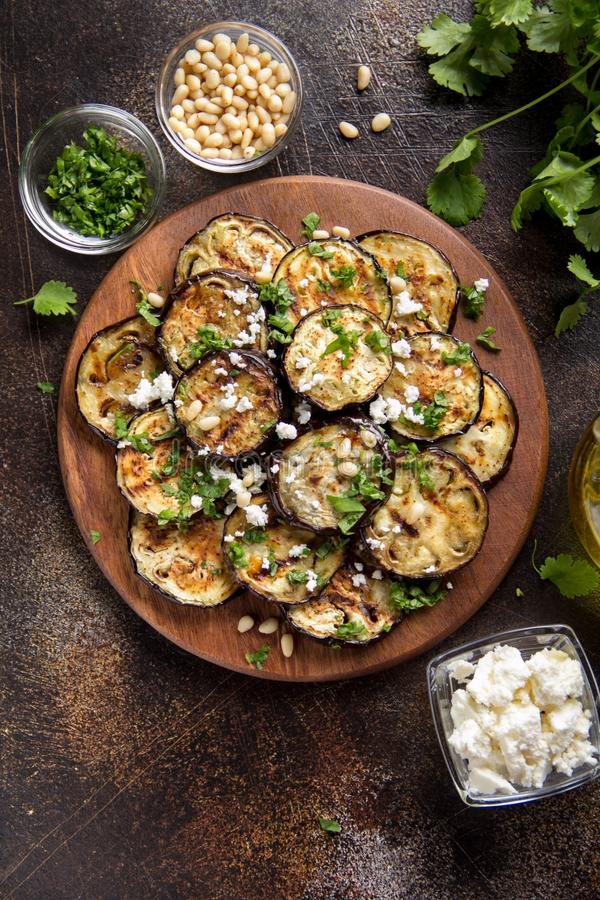 Зажаренный баклажан с фета, гайками сосны, свежими травами (cilantro, петрушкой) и оливковым маслом Вкусная закуска овоща, лето,  стоковое изображение rf