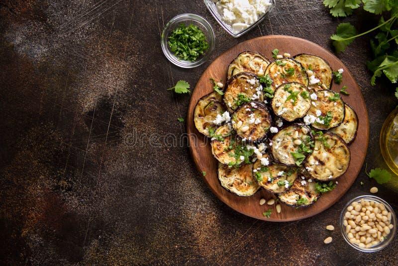 Зажаренный баклажан с фета, гайками сосны, свежими травами (cilantro, петрушкой) и оливковым маслом Вкусная закуска овоща, лето,  стоковые фото