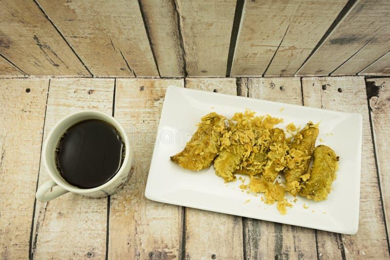 Зажаренный банан (Pisang Goreng), традиционная закуска в Малайзии с черной кофейной чашкой стоковые фото