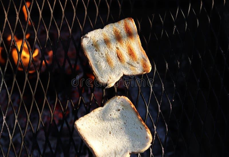 Зажаренный белый тост на особенном черном гриле для совершенно хрустящего деликатеса Жарящ тосты на среднем пламени сделанном дер стоковые изображения