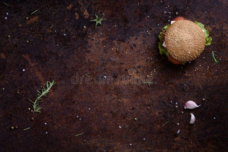 Зажаренный бургер говядины с салатом и майонезом на деревенских таблице или счетчике Copyspace, плоское положение, над взглядом стоковое фото