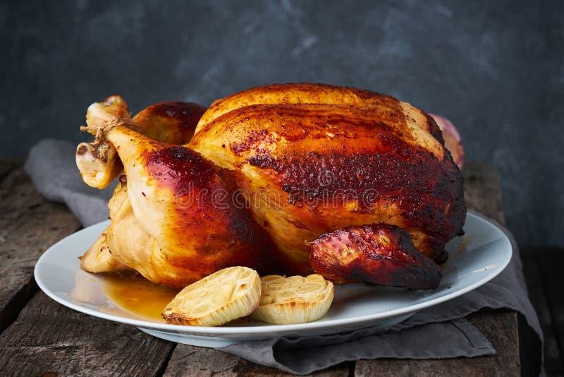 Зажаренный весь цыпленок в голубом сотейнике на темном - серый старый деревянный стол, испеченное мясо с картошками Взгляд со сто стоковая фотография