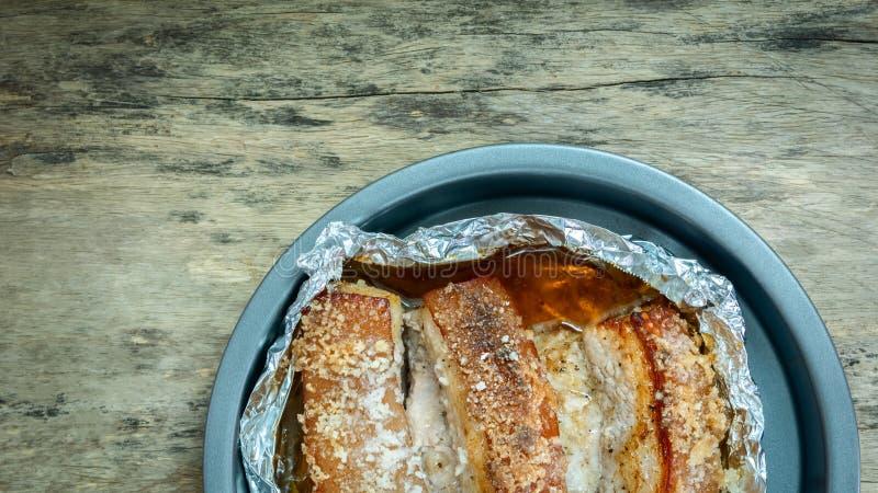 Зажаренный в духовке кудрявый свинина в блюде на деревянном столе стоковые изображения