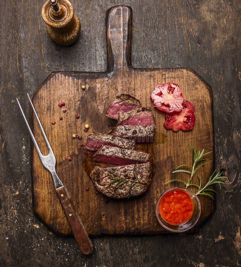 Зажаренный в духовке стейк ribeye отрезал ‹â€ ‹â€ на разделочной доске с вилкой, красным соусом, перцами и томатами на деревенско стоковое изображение rf
