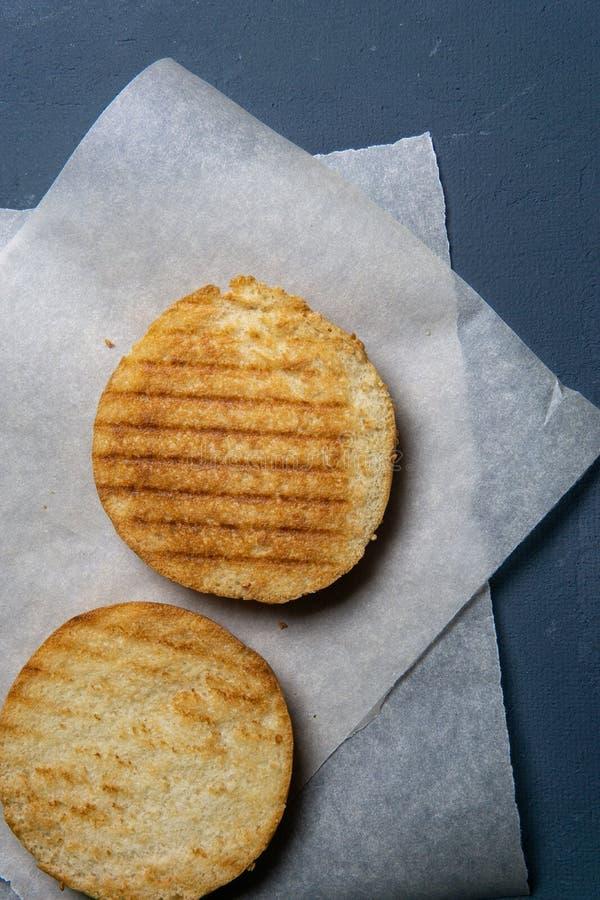 зажаренный и отрезок в половинной плюшке бургера на бумаге стоковые фотографии rf