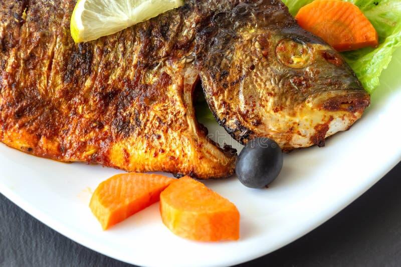 Зажаренный лещ моря рыб с овощами на белой плите Темная предпосылка шифера Концепция еды здорового питания стоковые фотографии rf