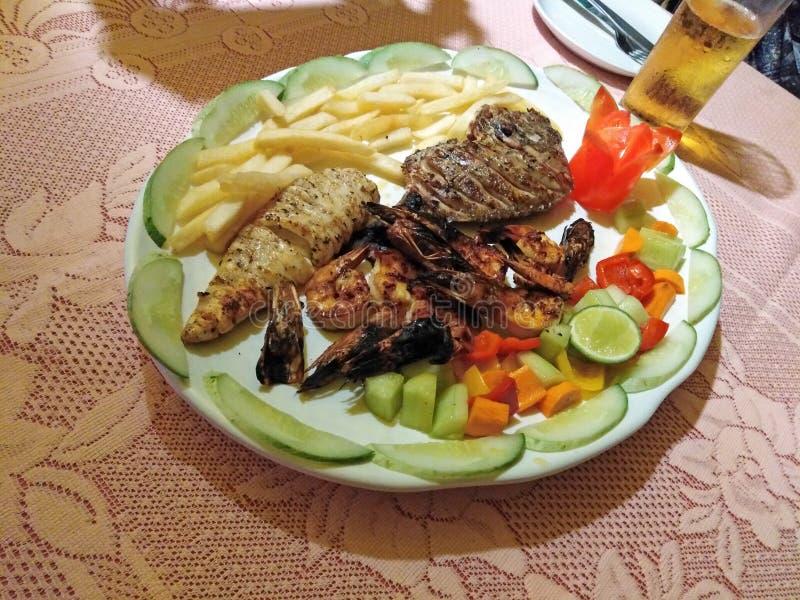 Зажаренный продукт моря с овощами и французским картофелем фри в ресторане goa стоковая фотография