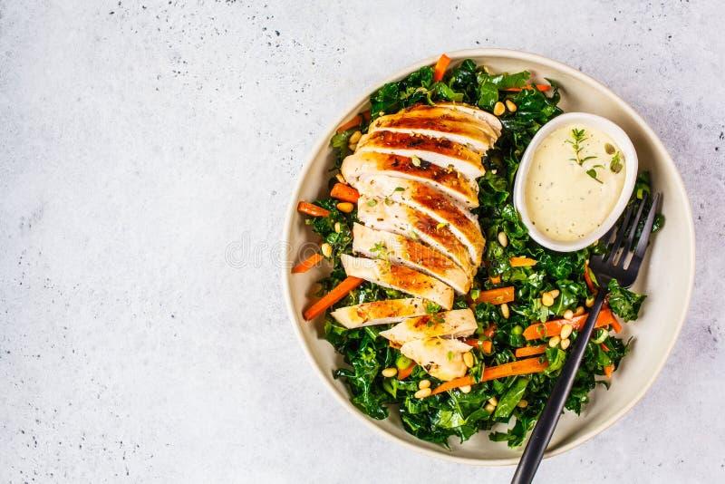 Зажаренный салат куриной грудки с листовой капустой, гайками сосны и цезарем одевая в белой плите стоковая фотография rf